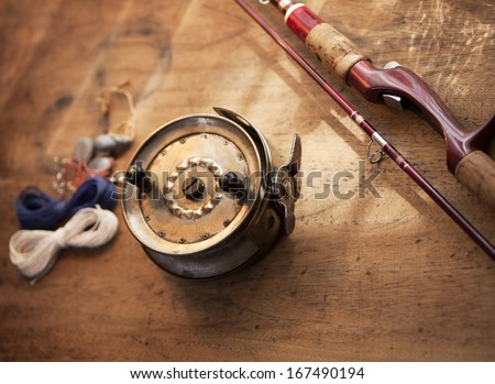 Vintage fishing reel, and rod on old wooden surface.  - stock photo