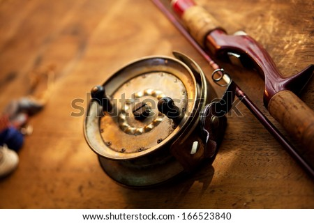 Vintage fishing reel, and rod on old wooden surface. Warm lighting. - stock photo