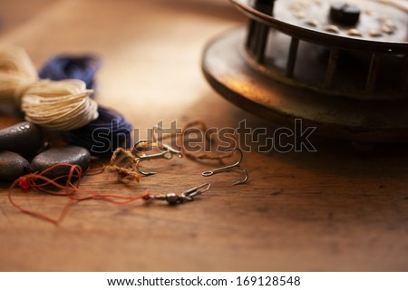 Vintage fishing reel, and treble hook on old wooden desk. - stock photo