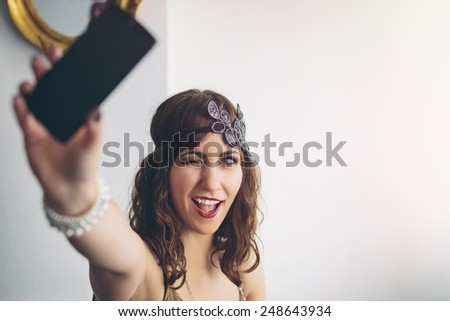 Vintage flapper girl using a modern smartphone iphon style for a selfie, contrast concept - stock photo
