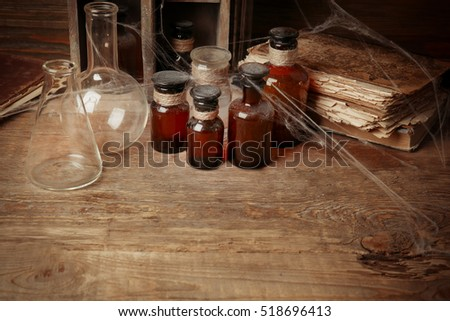 Vintage flasks and glass bottles with spiderweb on wooden background, closeup