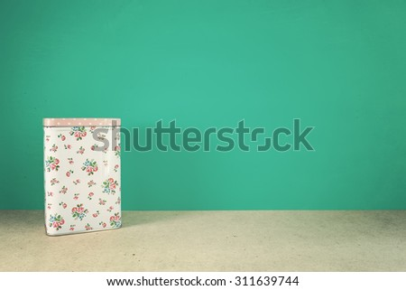 Vintage floral pattern packaging box on table front mint green background. Vintage effect. - stock photo