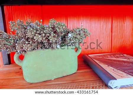 vintage flowers in pot on red wooden wall