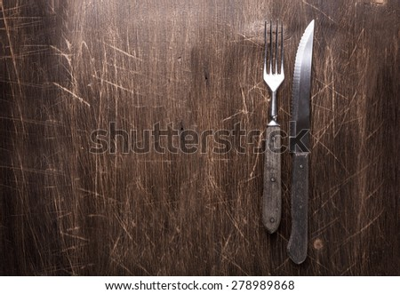 Vintage fork and knife on wooden tabletop - stock photo