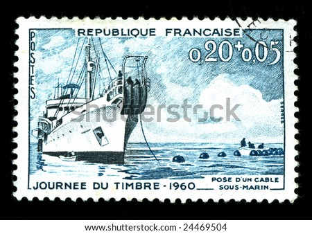 vintage french stamp depicting a cable laying ship - stock photo
