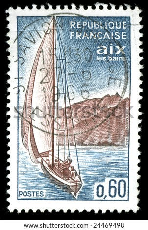 vintage french stamp depicting a sailing yacht sailing along a coastline - stock photo