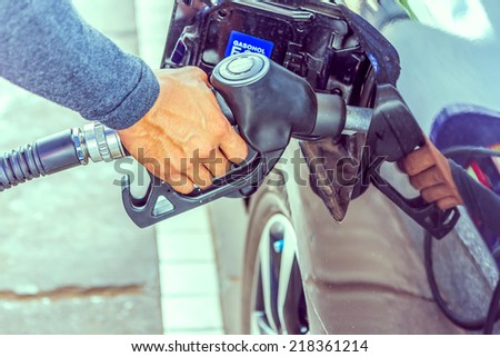 Vintage Fuel nozzle add fuel in car at gas station - stock photo