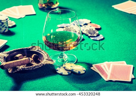 Vintage gambling table with whiskey, cigar and cards - stock photo