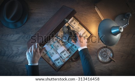 Vintage gangster with a gun and a leather briefcase filled with dollar packs, top view, 1950s film noir style - stock photo