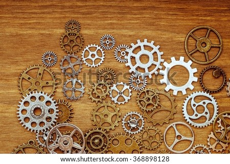 vintage gear wheels on wooden background - stock photo