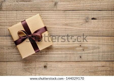 Vintage gift box with bow on wooden background - stock photo