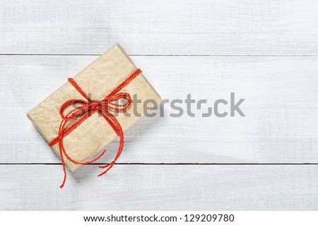 Vintage gift box with red ribbon on wooden background - stock photo