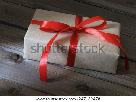 Vintage gift box wrapped in kraft paper on wooden background