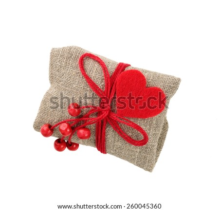 vintage gift in sacking with red heart and beads, isolated on white - stock photo