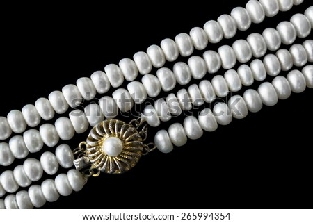 Vintage gilded clasp on pearl necklace isolated over black - stock photo