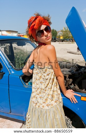 Vintage girl posing in front of the car summer day