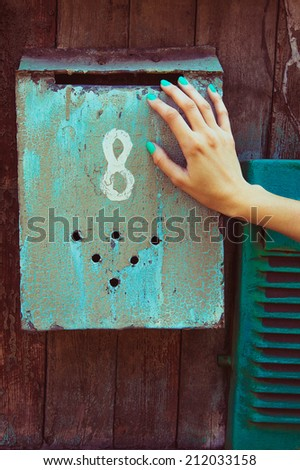 Vintage glamorous manicure concept. Girl's hand with trendy nail color over old retro mailbox number eight. Outdoor fashion shot. - stock photo