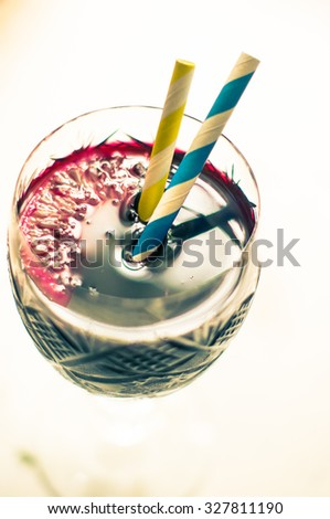 Vintage glass of mulled wine with straws on the old wooden background. Toned picture