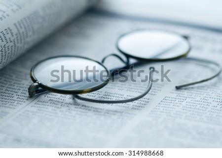 vintage glasses on newspaper - stock photo