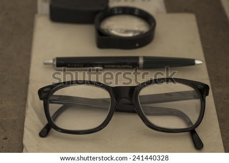 Vintage glasses, pen and magnifier close up - stock photo