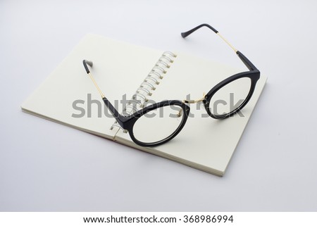vintage glasses with notebook on white background