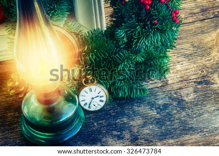 vintage glowing lantern with christmas evergreen wreath and antique watch, low key - stock photo