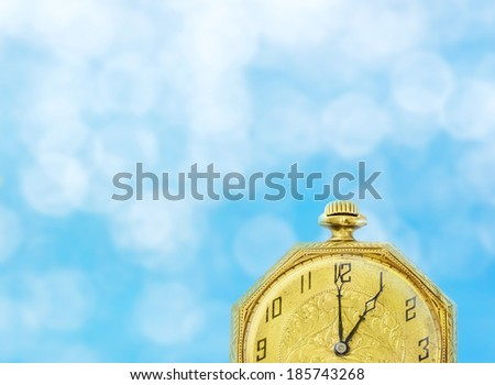 Vintage gold color pocket watch on blue sky with clouds bokeh background. Time passing concept. Horizontal composite photograph.  - stock photo