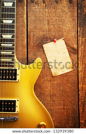 Vintage gold top single cutaway guitar on old wood surface and blank piece of paper, good for playlists, and production notes. - stock photo