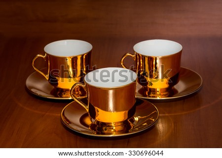 vintage golden coffee cups on wooden background