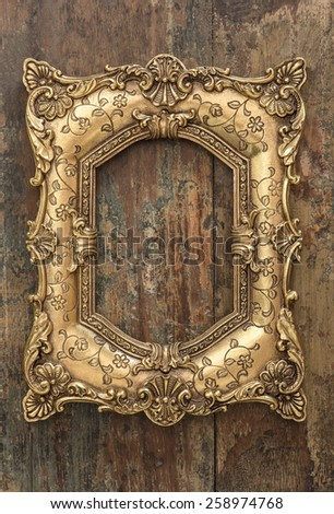Vintage golden frame on wooden background. Grunge wood texture. Selective focus on picture frame - stock photo