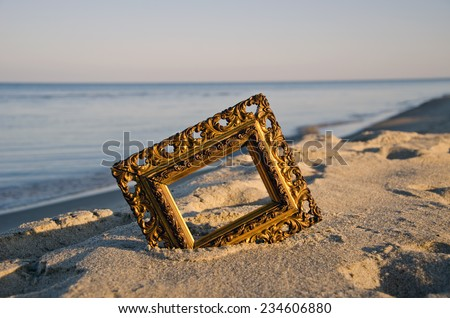 vintage golden picture frame on sea resort beach in sunrise light - stock photo