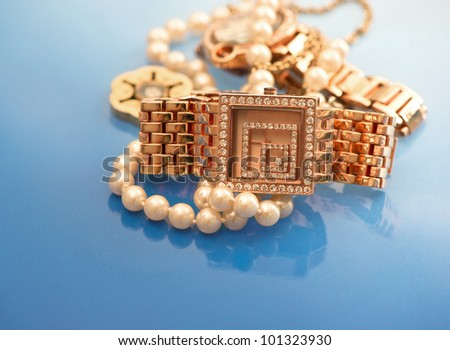 vintage golden watch with gems and jewelry on blue background. selective focus - stock photo