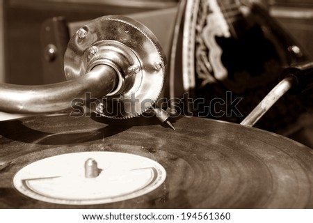 Vintage gramophone with a vinyl. Sepia - stock photo