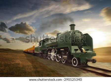 vintage green and yellow steam powered railway train moving - stock photo