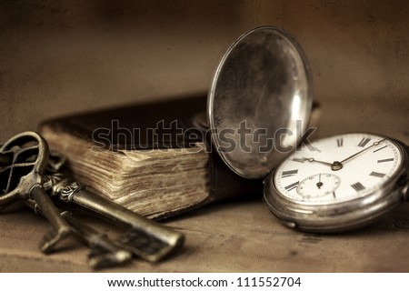 Vintage grunge still life with pocket watch, and old book and brass keys. - stock photo