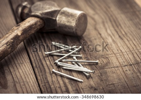 Vintage hammer and nails lying on wooden surface of workbench. Conceptual image of home improvement, DIY and carpentry. - stock photo
