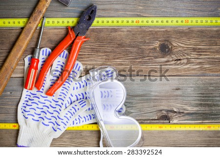 vintage hammer, pliers, screwdriver, tape measure, gloves and safety glasses on old textured boards bench. still life with working tools - stock photo