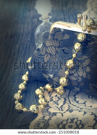 vintage handbag with shiny pearls on the wooden background - stock photo