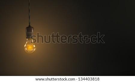 Vintage hanging light bulb over dark background - stock photo