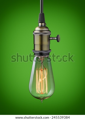 Vintage hanging light bulb over green background  - stock photo