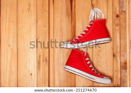 Vintage hanging shoes tied on wooden background - stock photo