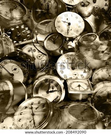 Vintage heap of alarm clocks in sepia. - stock photo
