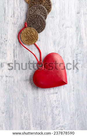 Vintage heart decoration and old coins on light blue background - stock photo