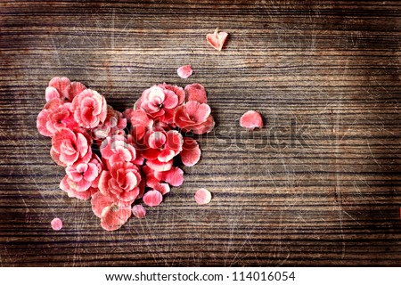 vintage heart from flowers   on wooden table/vintage valentin day background - stock photo