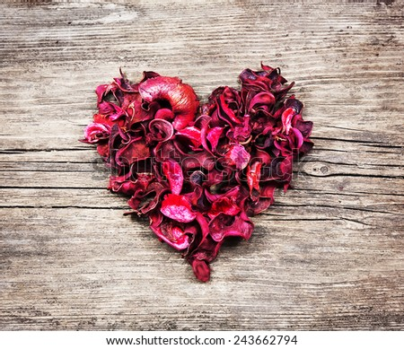 Vintage heart from red dry petals on wooden table - stock photo