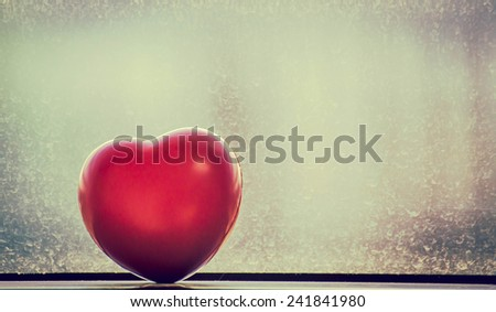 Vintage Heart-shaped of red translucent  against window with old background. - stock photo