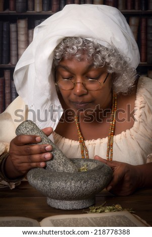 Vintage herbalist working with mortar and pestle - stock photo