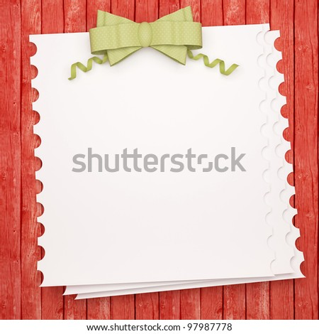 Vintage holiday paper background with green bow, white invitation blank in front of red wooden wall for insert your text (design).