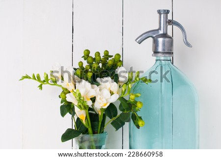 Vintage home decor, ancient turquoise siphon, freesias bouquet and bottles on a white wooden background. - stock photo