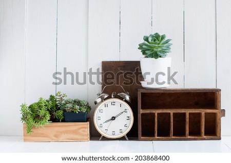 Vintage home decor: old wooden boxes, houseplants, alarm clock on white wooden board, retro home interior. - stock photo